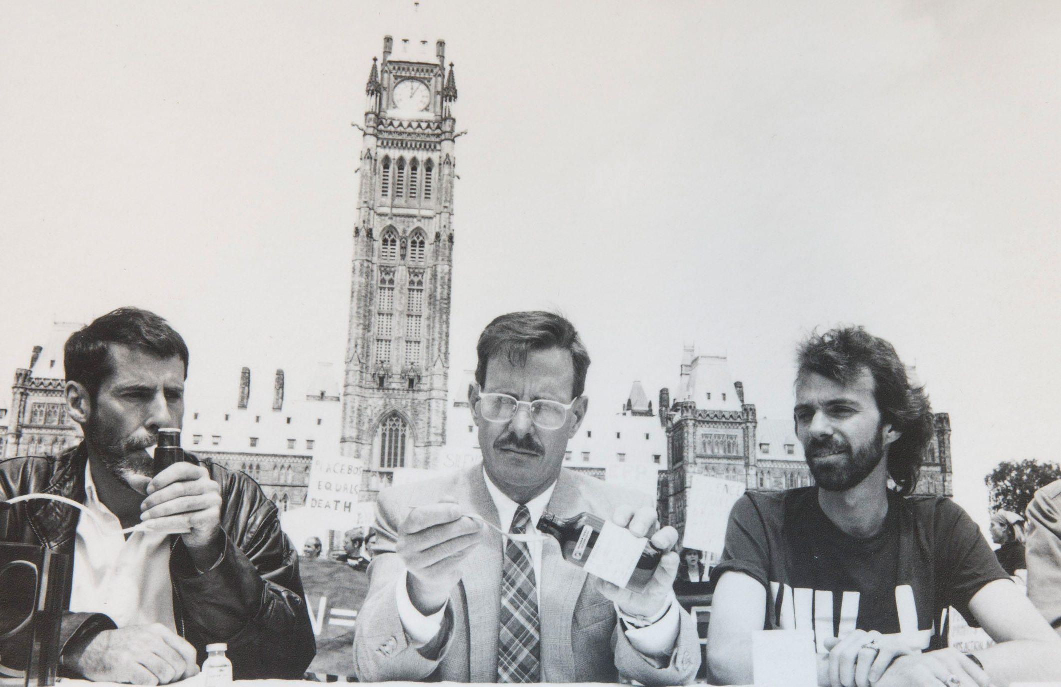PARLIAMENT HILL PROTEST — From left: in 1988, Bill Greenway, Michael Lynch, and James Thomas — members of AIDS Action Now — demonstrated the government's inaction in making experimental HIV/AIDS drugs available by taking four of the 24 drugs already available elsewhere in the world. Photo: Colin Rowe, courtesy of ACO