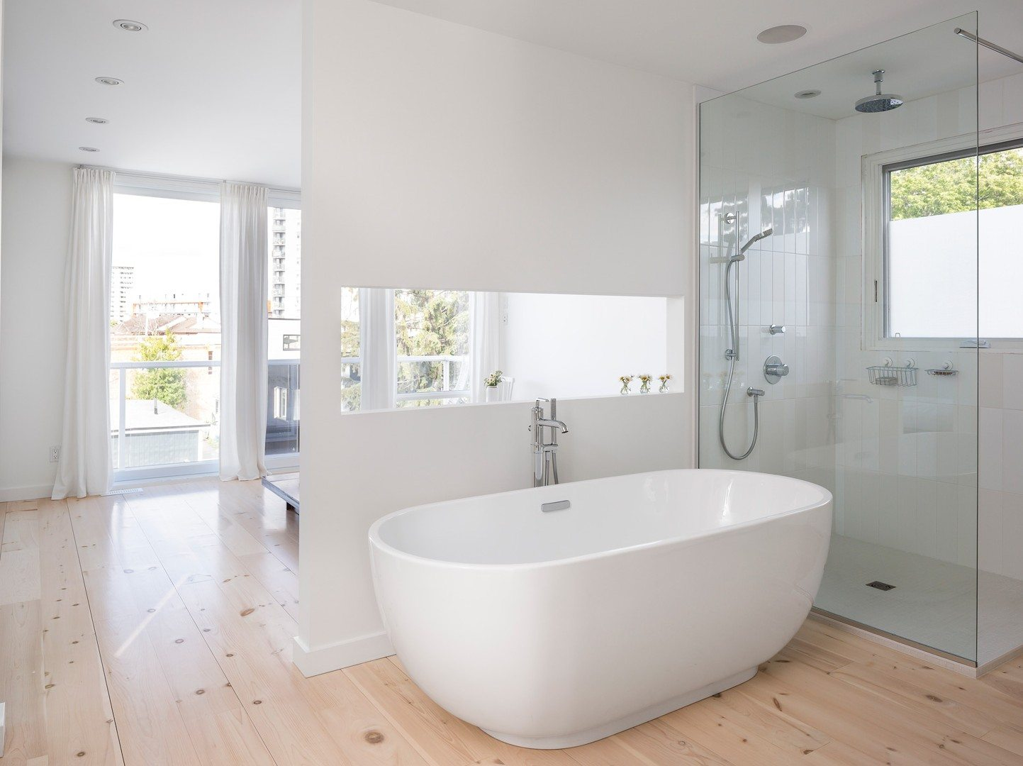 The bathroom illustrates the couple's aesthetic — clean but cozy. The gently rounded tub is set on warm pine floors, while the separate shower boasts tile. A powder room (not shown) allows for privacy. Photo: Doublespace Photography