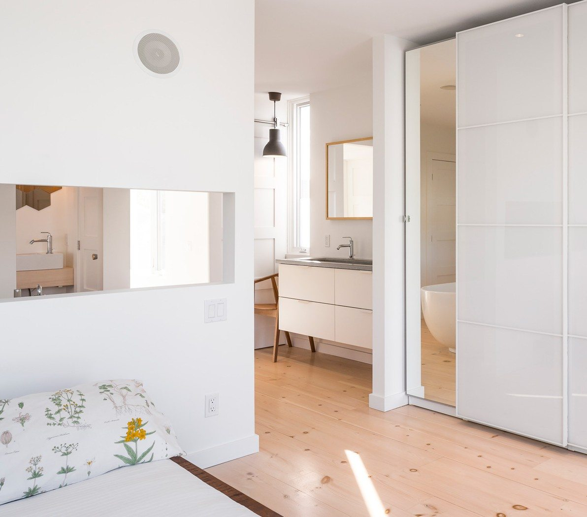 Located on the top floor, the master bedroom leads out onto an east-facing balcony. The cleverly designed cutout behind the bed allows light to stream into the ensuite bathroom, just behind the wall. Photo: Doublespace Photography