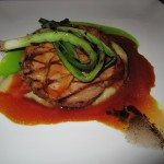 Echine de porc marinated in maple with burnt onion oil, grilled green onions, jus, and while vegetable puree