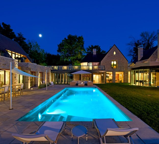 Facing page: The main house (a portion of which is visible in the top right corner of the photograph) is centred around two original stone barns that were renovated and incorporated into one larger design. The new section is an indoor-outdoor space connected to the house by a glass corridor. Photo by Doublespace Photography.