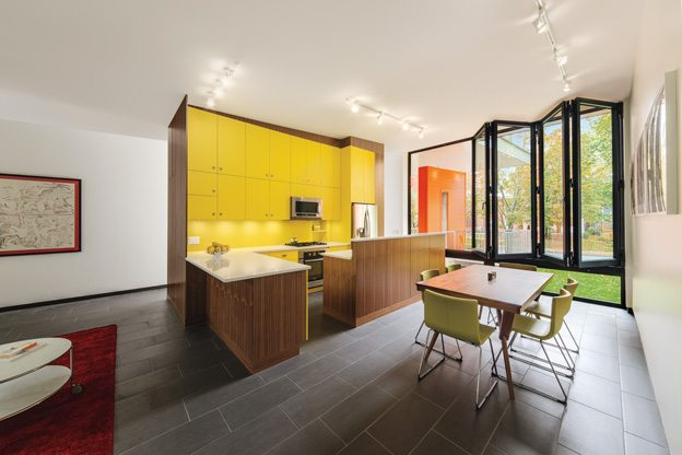 The family is fearless when it comes to colour, but countered the intensity of the yellow cabinetry with warm walnut accents. Photography by PhotoluxStudio.com - Christian Lalonde