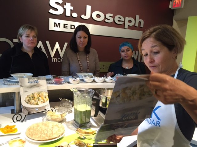 Chef Heather Trim shows off some of the recipes in this year's milk calendar as our readers, from left, Janet Dempsey, Céline Forgues and Shamima Khan, look on.