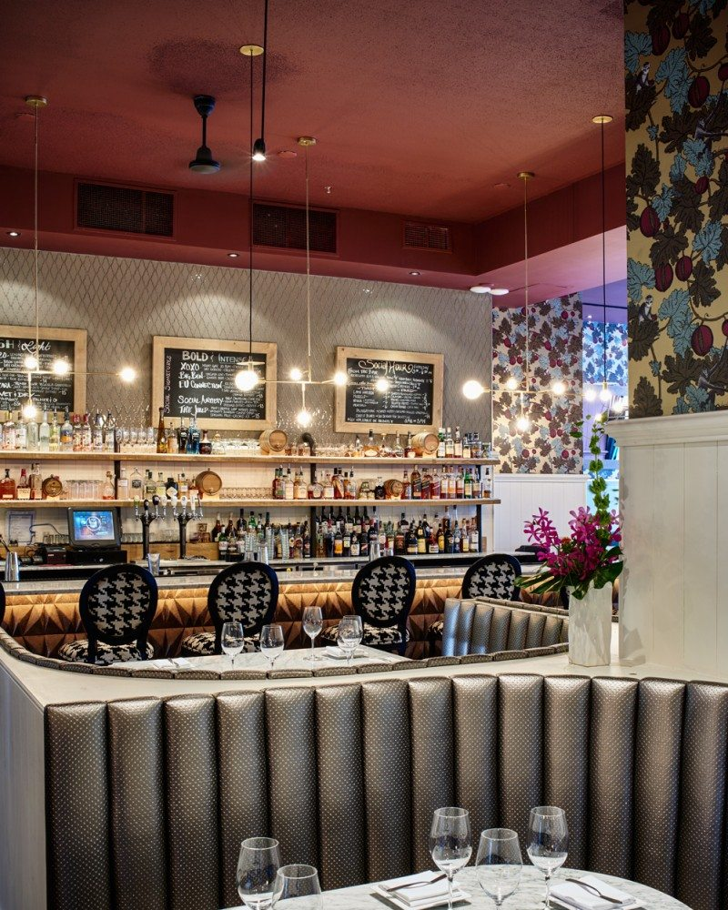 The new open bar area allows light to flood in from the front windows. Bold wallpaper and sparkly vinyl booths bring chic drama to the space, while blackboards and open shelving add a bistro feel.