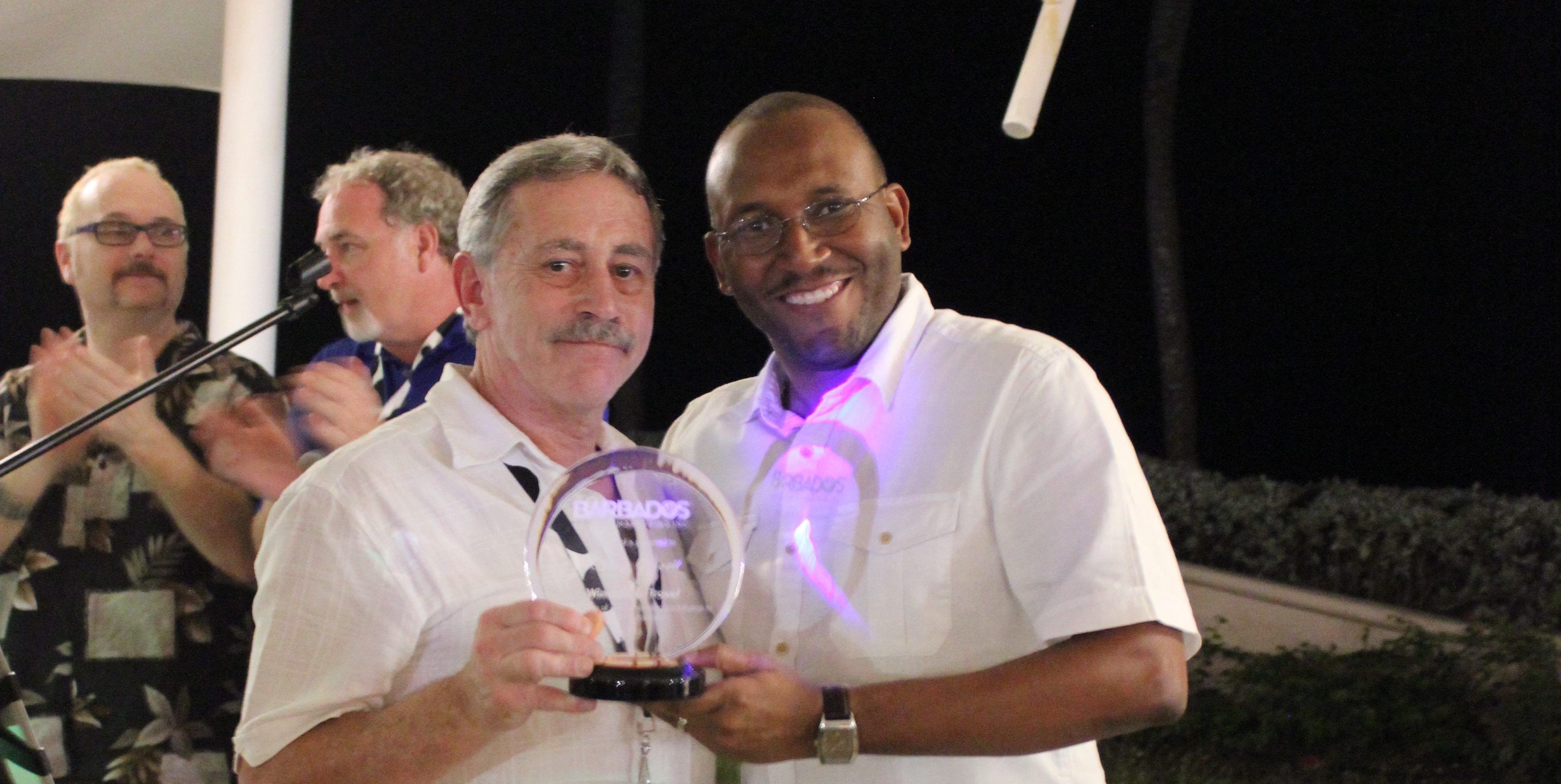 Winchester travel organizer Owen Shortt receives an award from Peter Mayers of Barbados Tourism Marketing Inc. Photo by Kimberley Johnson, Ottawa Magazine.