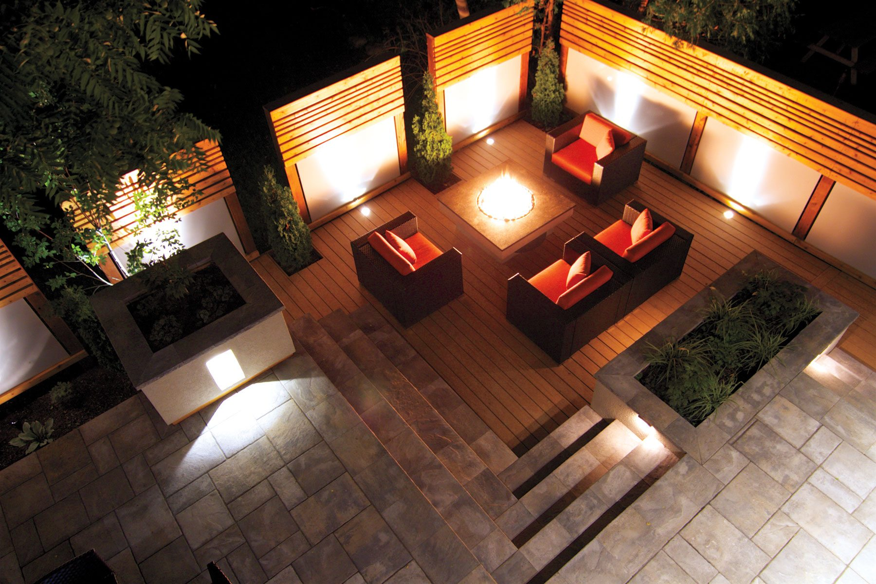 Soft lighting makes the area accessible day or night, while well-spaced screens afford some privacy but don't block the sun. The stone steps lead to a dining and barbecue area at the back of the house