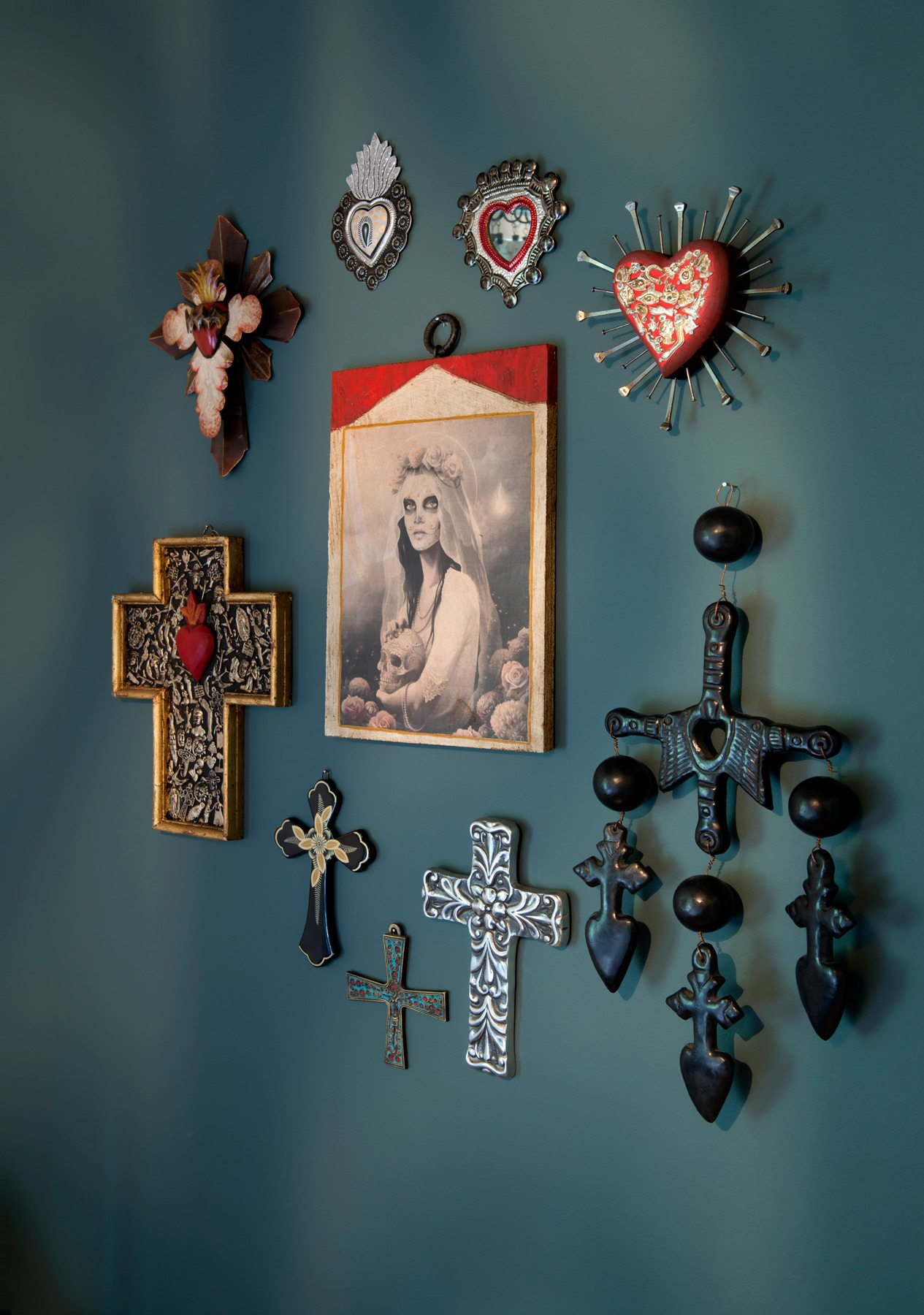 Christian symbols meet punk in the guest bedroom with its quirky display of religious artifacts, the highlight being a Day of the Dead image. Photography: Marc Fowler / Metropolis Studio