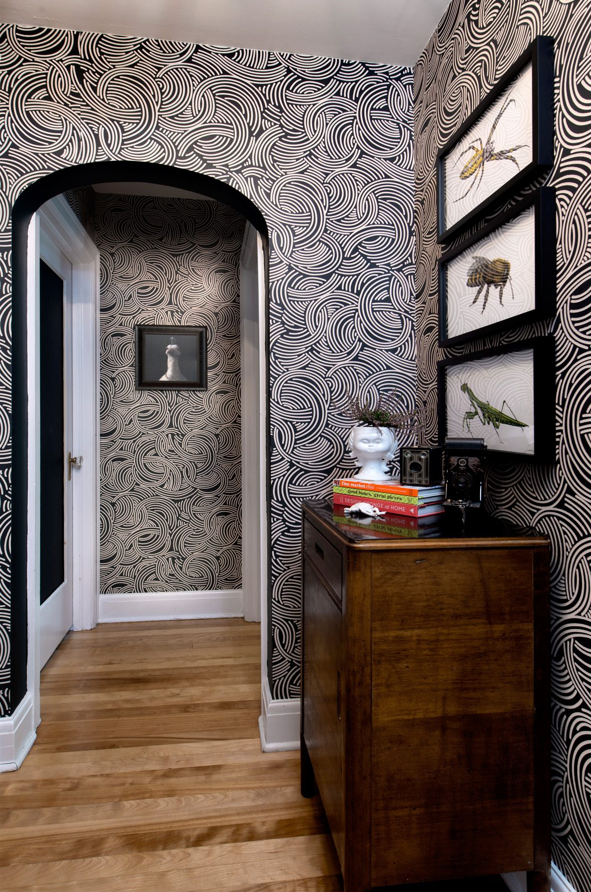 The Farrow & Ball wallpaper that starts in the downstairs hall continues up to the second-floor hallway. The three framed creepy-crawlies, by local illustrator Graham Spaull, seem to be content on their busy black-and-white background. Photography: Marc Fowler / Metropolis Studio