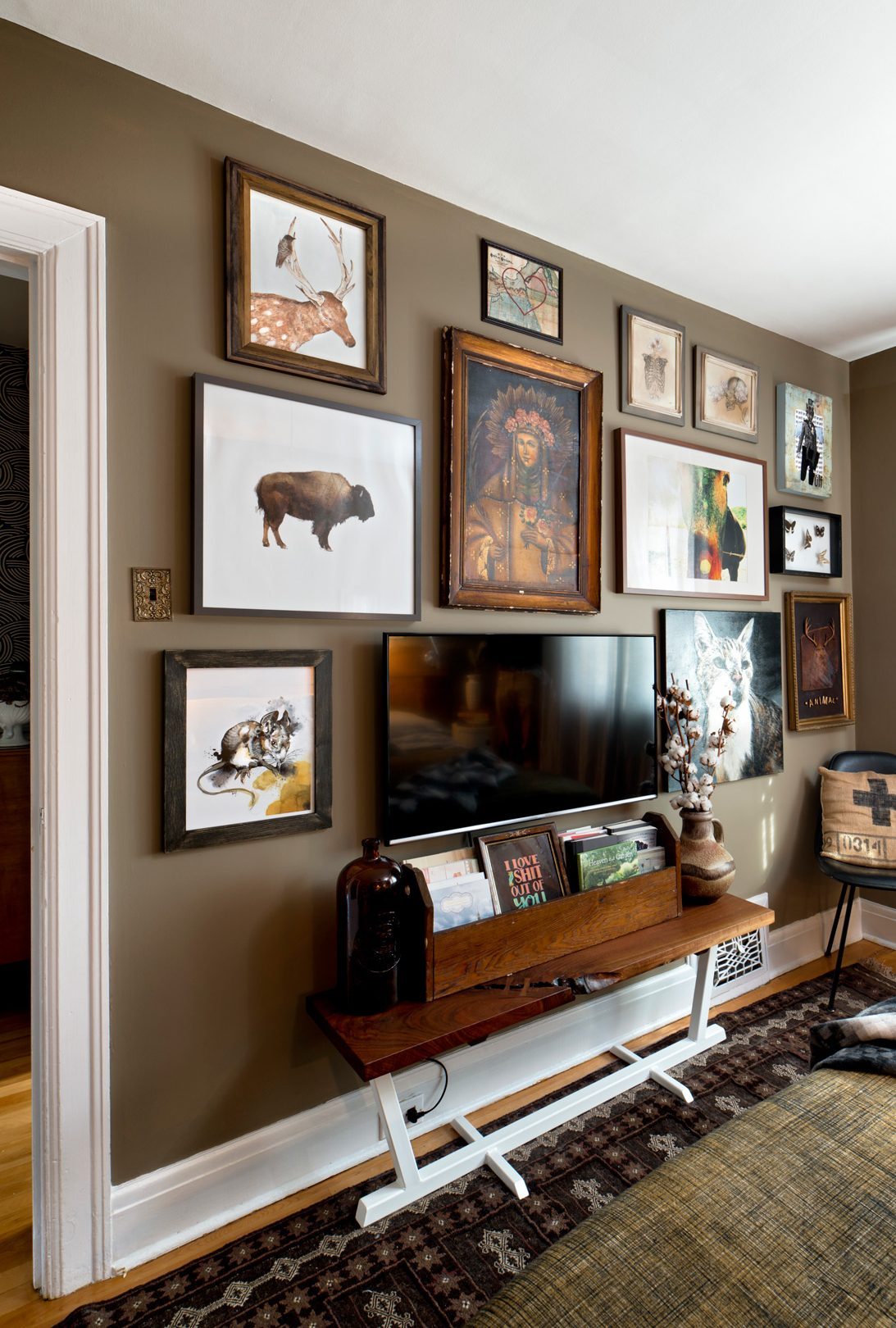 On one wall of the master bedroom a table refurbished by Jeff sits below the television, while a gallery of interesting art finds livens up the room. Photography: Marc Fowler / Metropolis Studio