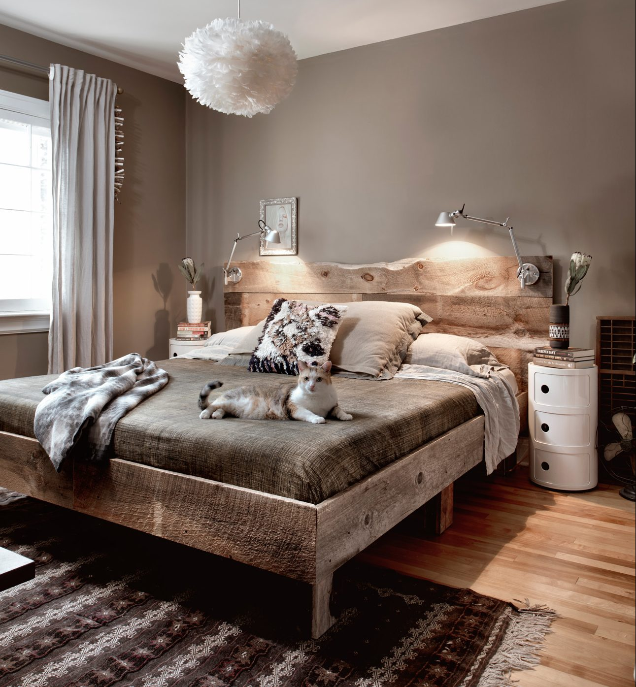 Jeff built the bed frame in the master bedroom from old barnwood, making for a rustic feel. With white trim and rich, dark walls, the room is enveloping and warm. Photography: Marc Fowler / Metropolis Studio