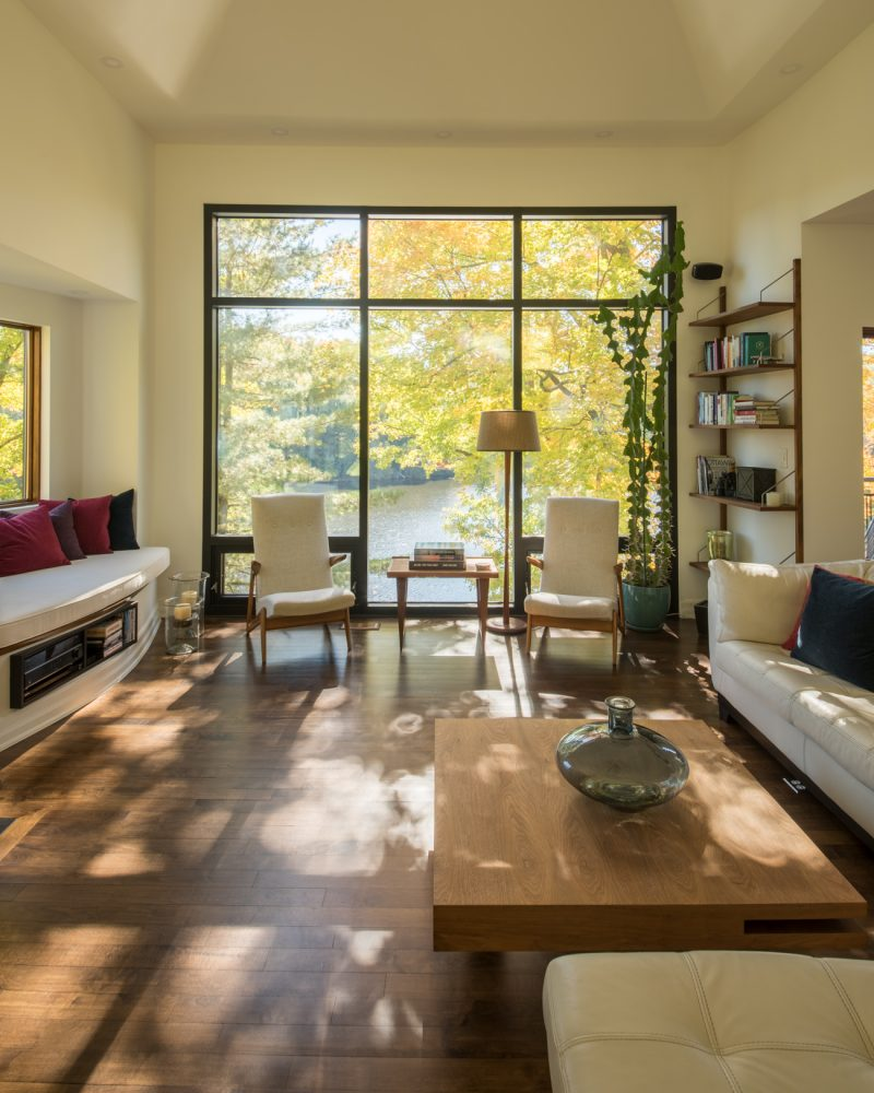 """A view of the living room looking out towards the river, where  the glass """"wall"""" frames a vast expanse of trees and water. The pair of 1950s walnut Grasshopper chairs from Belgium are one of Gordon's favourite furniture finds. Photography PhotoluxStudio.com — Christian Lalonde"""