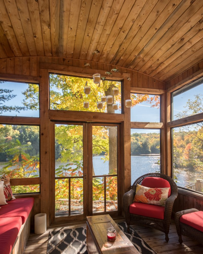The screened-in porch on the lower level opens directly to a path leading to the river. The room has a resolutely cottage-like atmosphere — the perfect spot to take a nap or read, free from mosquitoes. Photography PhotoluxStudio.com — Christian Lalonde