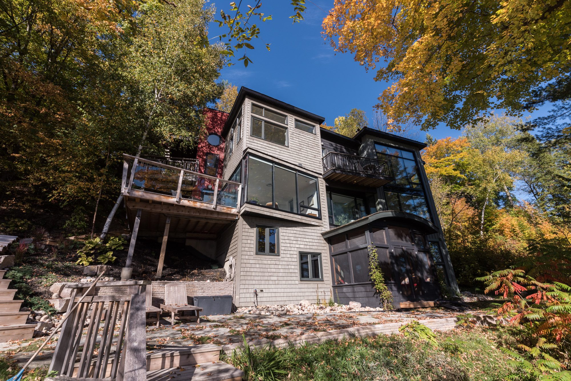 A view of the cottage exterior taken from the banks of the Gatineau River shows  the eccentric angles and varied finishes. Photography PhotoluxStudio.com — Christian Lalonde