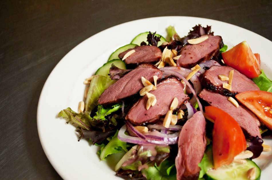 The Arrow & Loon pub puts smoked duck breast together with almonds, mixed greens, and a raspberry vinaigrette