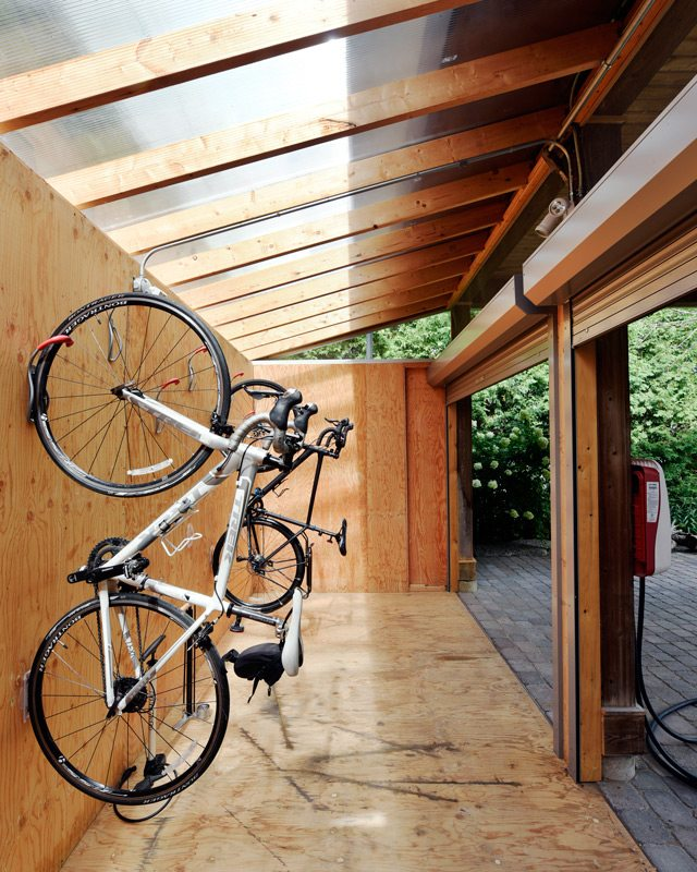 A sloped polycarbonate roof keeps the rain out and allows light to flow in during daylight hours. The space above the garage doors is intentionally left open to the elements to allow air to circulate. Photo: Gordon King