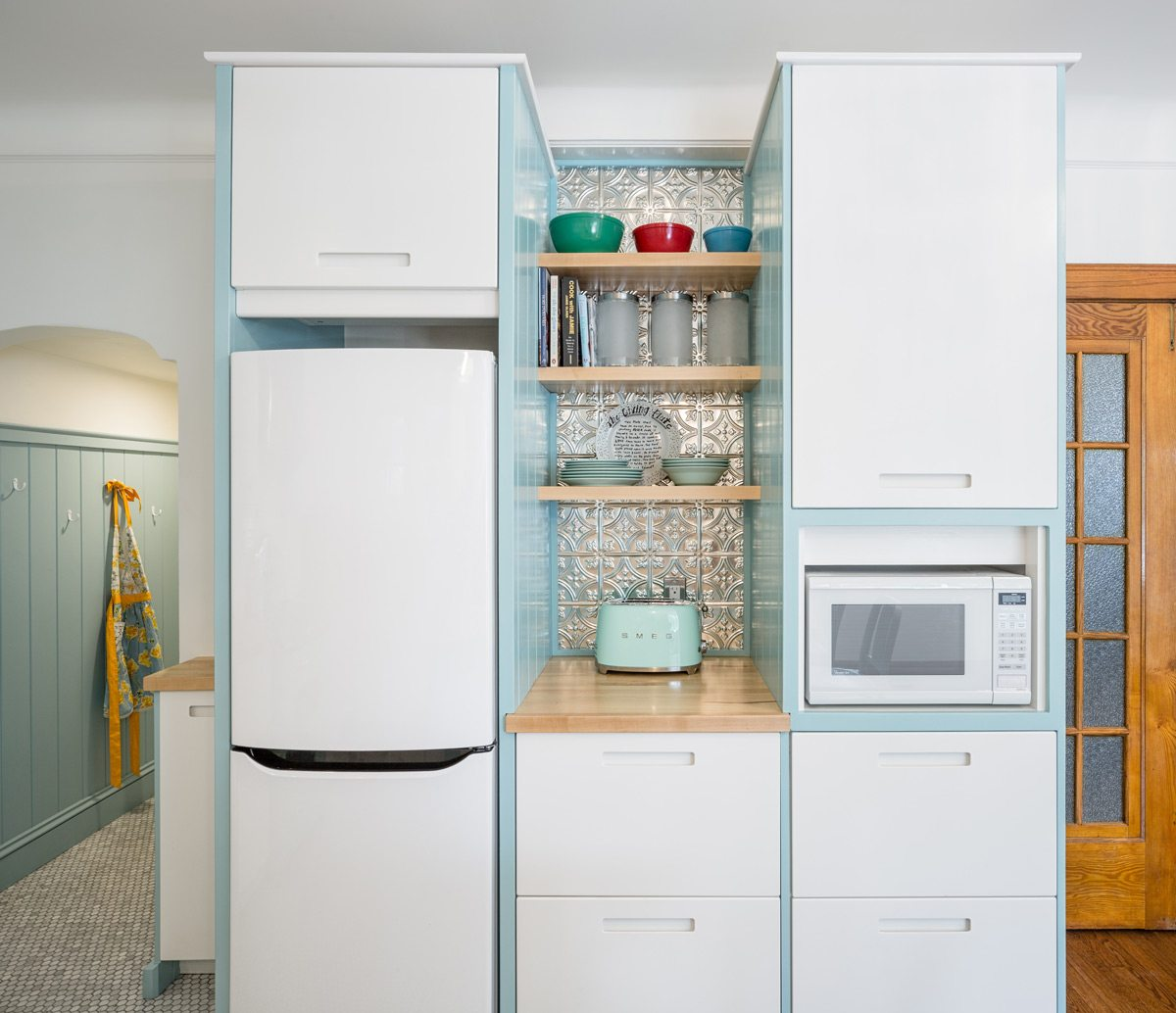 Painted a soft baby blue, beadboard frames the Ikea cabinetry, adding personality and a pop of colour. The custom maple shelves add a warm element and match the counters. Photo: Justin Van Leeuwen